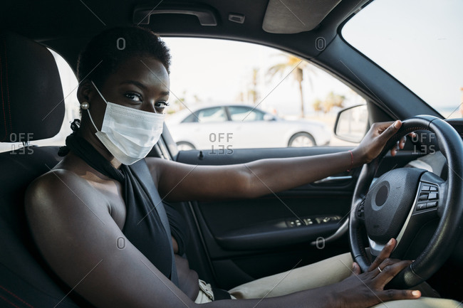Woman with protective face mask driving car