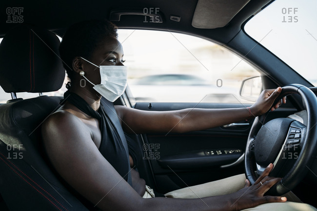 Young woman wearing face mask concentrating on driving car