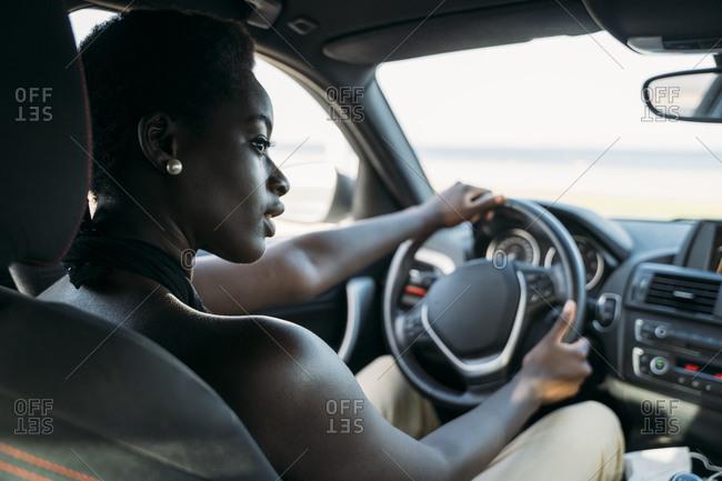 Beautiful woman looking away while driving car