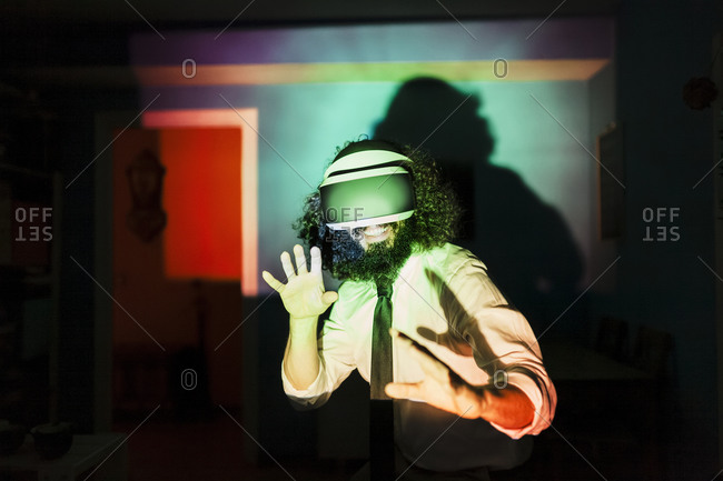 Smiling man wearing virtual reality glasses standing in multi colored light reflection at home during pandemic