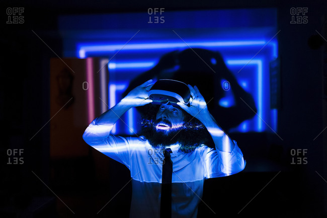 Man removing virtual reality glasses while standing at home during pandemic during pandemic