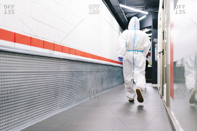 Healthcare man walking while wearing protective suit in hospital