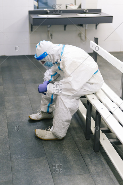 Contemplating man wearing protective suit sitting on bench in hospital