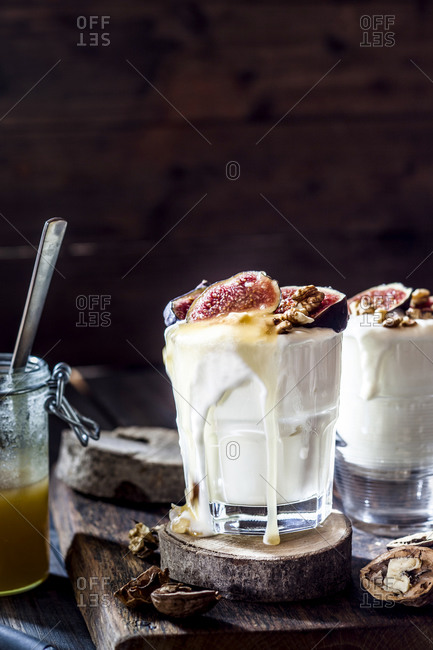 Two glasses of Greek yogurt with honey- figs and walnuts