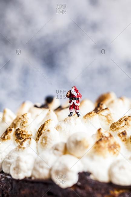 Santa Claus miniature standing on top of meringues of rhubarb cheesecake
