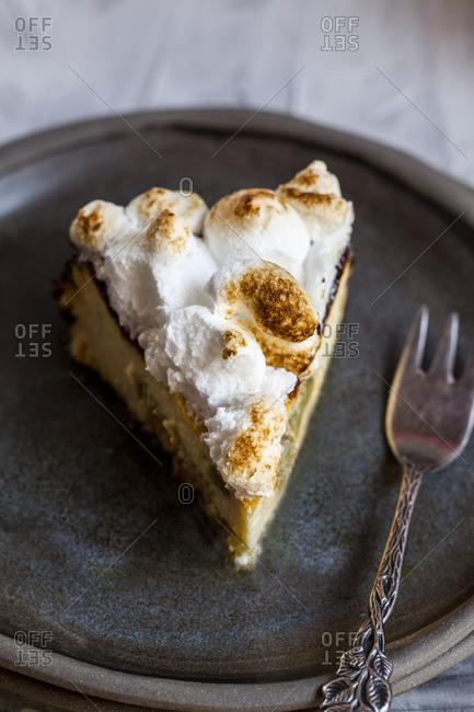 Slice of rhubarb cheesecake with meringues