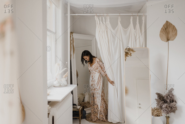 Young bride trying on wedding dress while standing at home