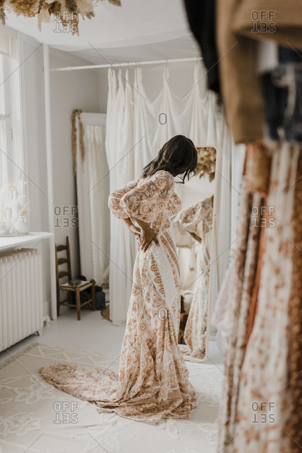 Young bride trying on wedding dress looking in mirror while standing at home