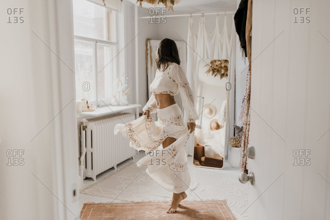 Young bride spinning her skirt while standing at home