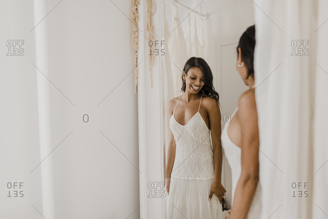 Smiling bride looking in mirror while standing at home