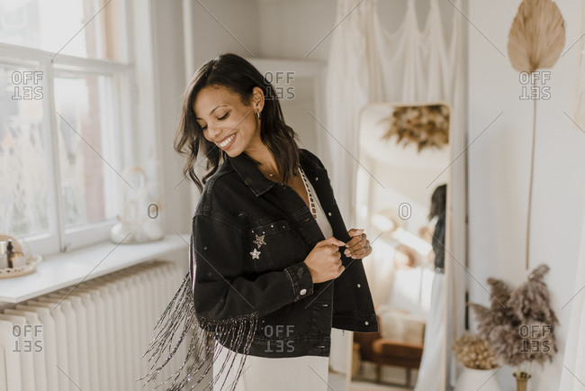 Bride looking down wearing jacket while standing at home