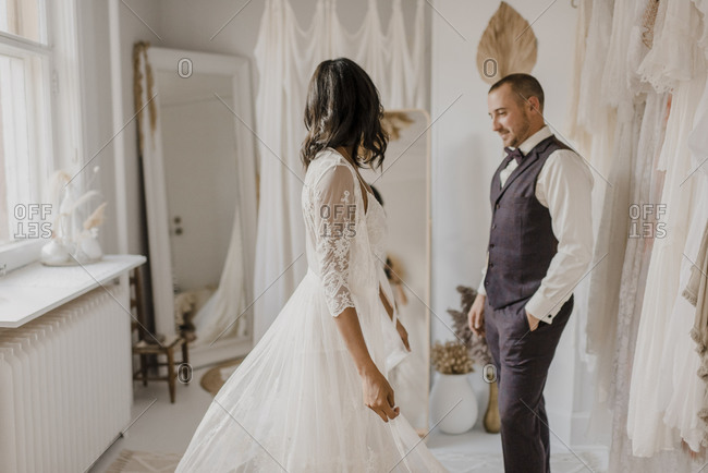 Young bride looking in mirror while bridegroom standing with hands in pocket at home