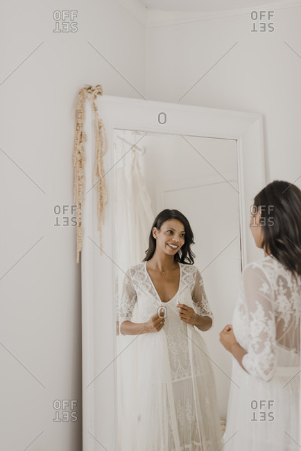 Reflection of young bride looking in mirror at home