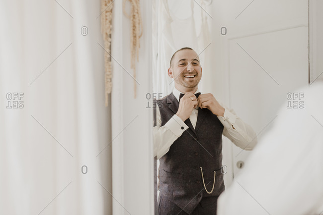 Bridegroom adjusting bow while looking in mirror at home