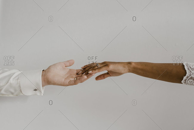 Cropped image of couple hand against wall