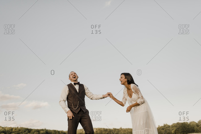 Cheerful couple laughing while standing at agricultural field