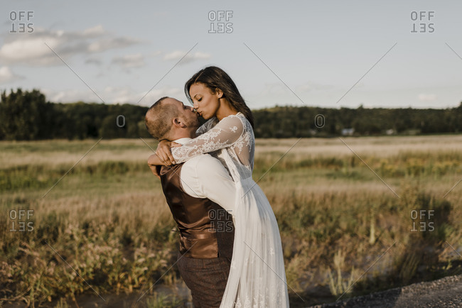 Heterosexual couple kissing while standing at agricultural field