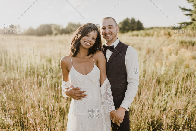 Smiling couple standing against agricultural field on sunny day