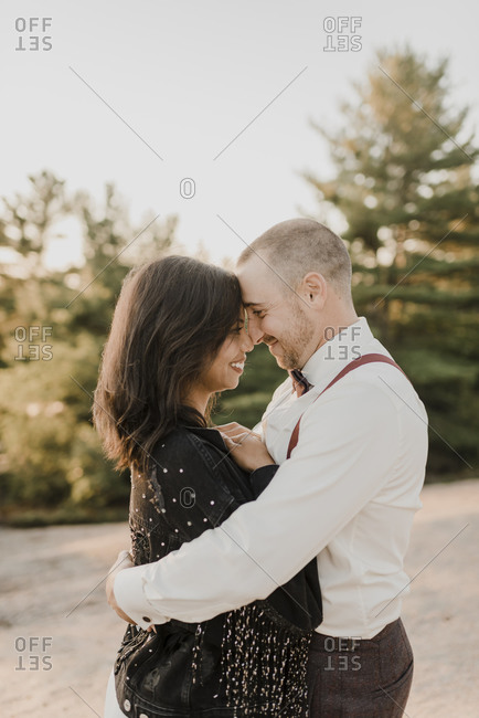 Couple embracing while nuzzling nose with each other in forest
