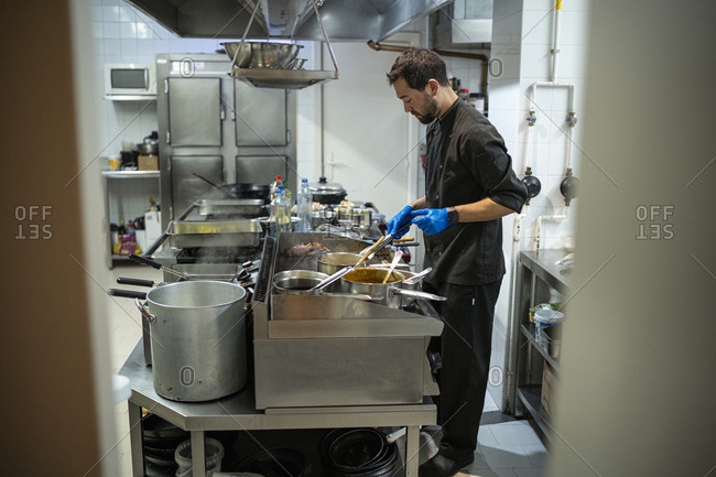 Man cooking while standing at commercial kitchen