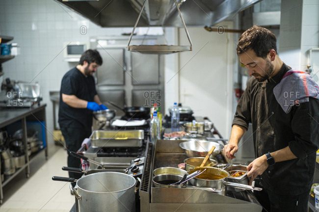 Chef standing by kitchen counter with coworker cooking in background at kitchen