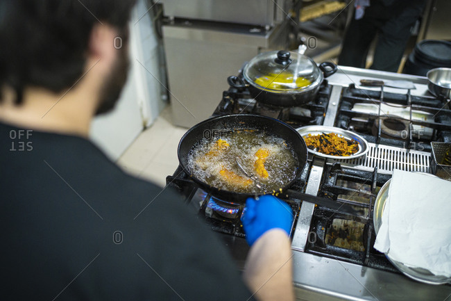 Chef frying food in cooking pan while standing at kitchen counter