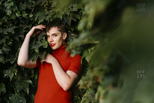Non-binary male smiling while standing against green leaves