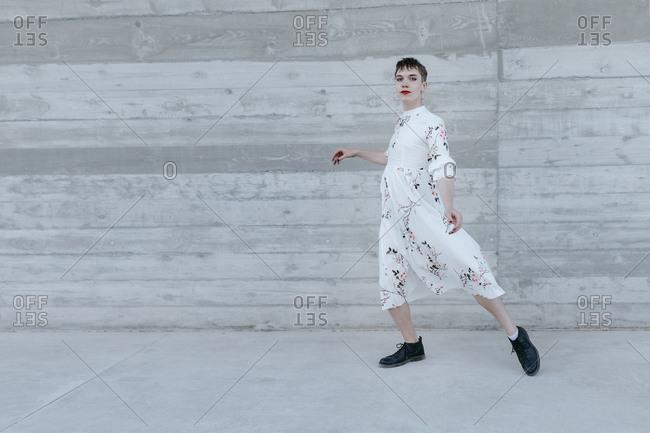Gender fluid man dancing against wall
