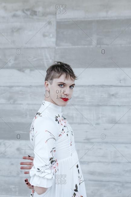Gender fluid man wearing white flower dress standing against wall