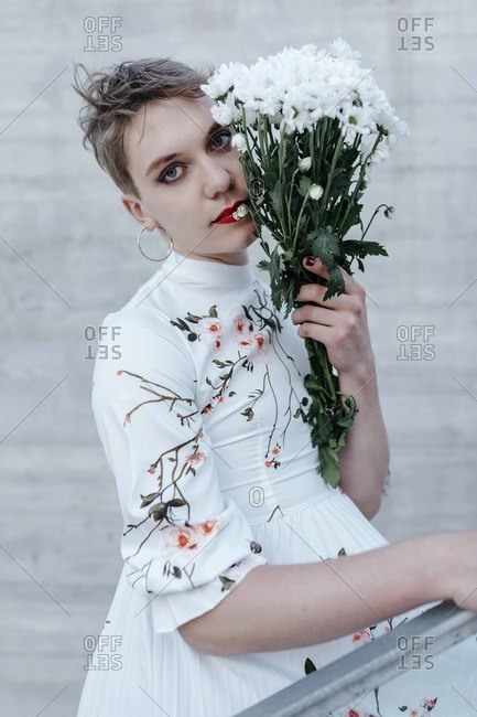 Young man holding bouquet of daisies while standing against wall