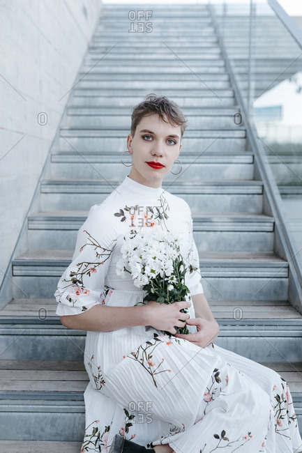 Gender fluid man holding bouquet of daisies while sitting on steps