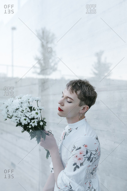Gender fluid man standing behind glass while holding bouquet of daisies against wall