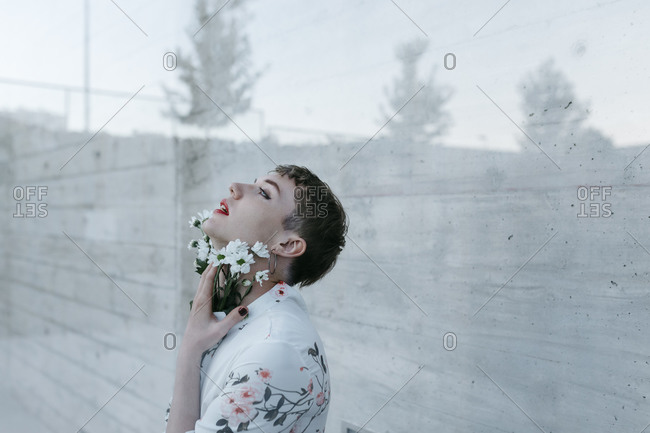 Gender fluid man standing behind glass while holding bouquet of daisies looking up against wall
