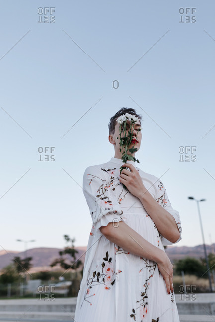 Gender fluid man covering face with bouquet of daisies while standing on street during sunset