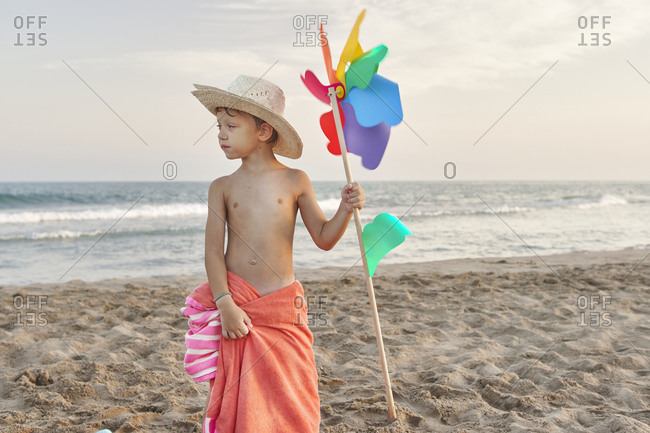 Boy wearing hat holding windmill toy while standing at beach