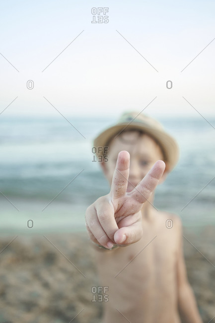 Boy showing peace gesture while standing at beach