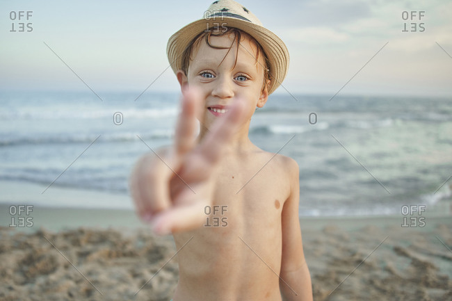 Smiling boy showing peace gesture while standing at beach