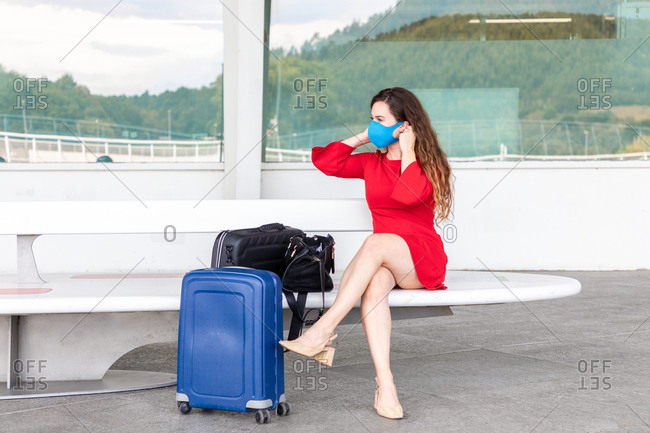 Serious female tourist putting on protective mask while sitting on bench with baggage in airport and looking away