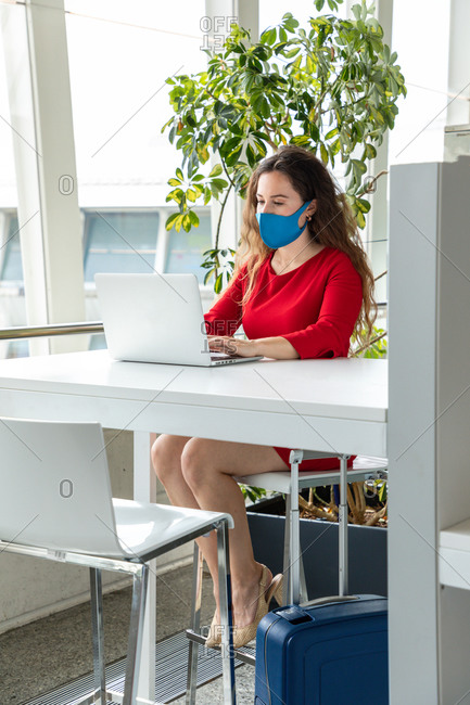 Serious female entrepreneur in protective mask sitting at table in workplace and typing on netbook while working on project during coronavirus pandemic