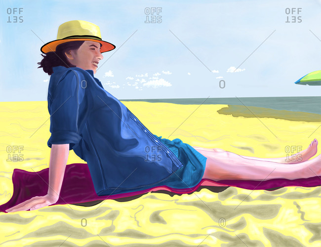 Woman in a straw hat reclining on beach sand by ocean on summer day