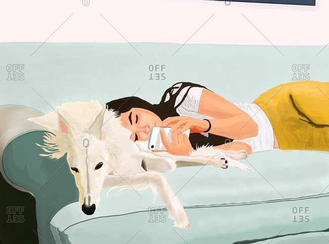 Girl lying on couch with dog using her cell phone