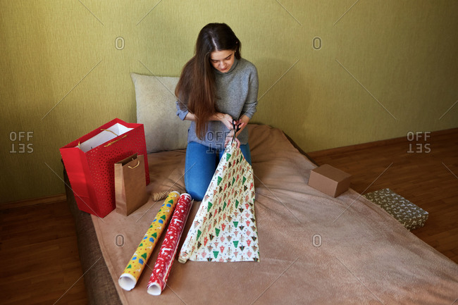 A young brunette woman preparing for Christmas by packing and decorating presents in wrapping paper at home