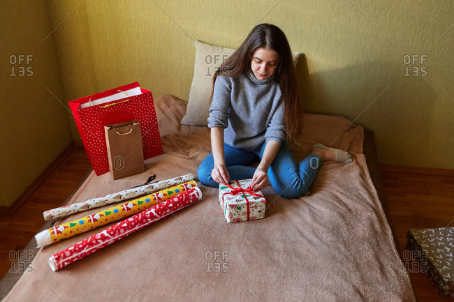 Young woman preparing for Christmas by wrapping presents in paper and bows at home