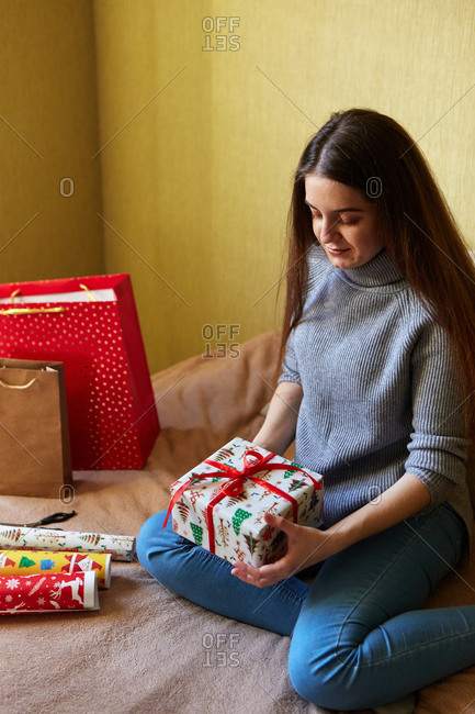 A young woman preparing for Christmas by wrapping gifts in paper and bows at home
