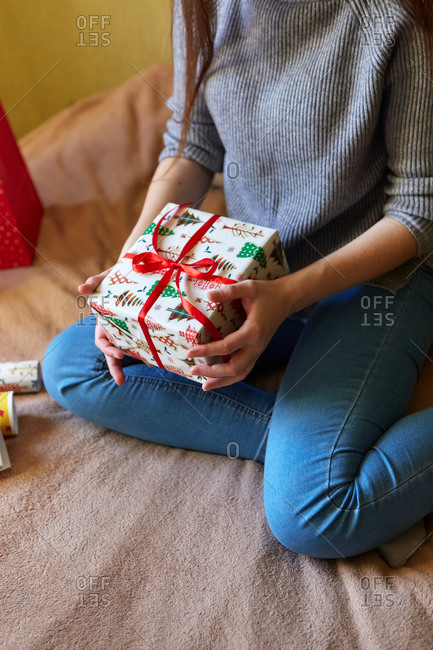 Close up of a young woman preparing for Christmas by wrapping gifts in paper and bows at home