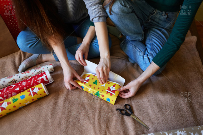 Two young women are preparing for Christmas by packing and decorating presents in wrapping paper at home