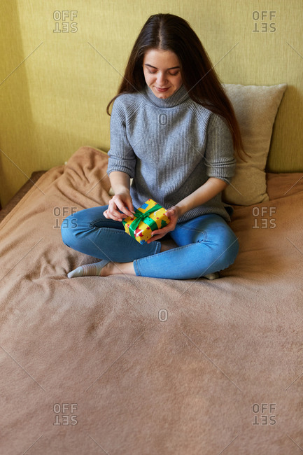 Young woman tying a bow onto a small Christmas gift that she wrapped at home