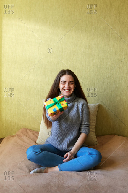 Joyful young woman holding a small Christmas gift that she wrapped at home