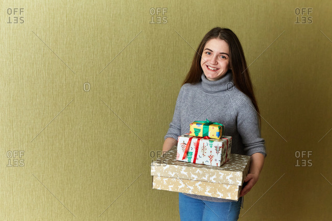 Portrait of a joyful young woman holding a stack of Christmas gifts that she decorated at home