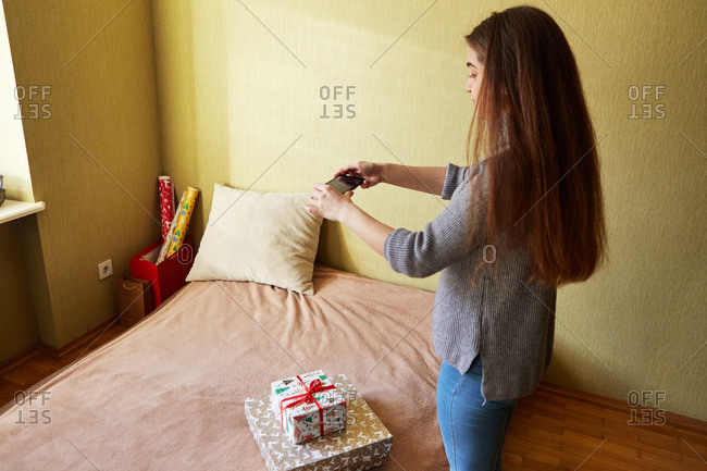 Young woman taking a photo of Christmas presents that are lying on a bed and are ready to be signed
